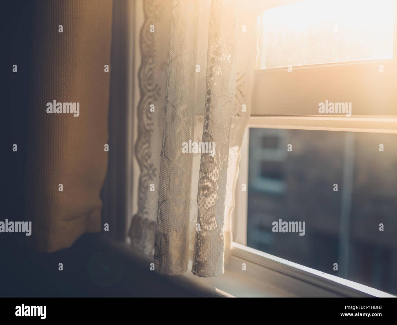 Sol de la tarde pegando una cortina a través de la ventana Imagen De Stock