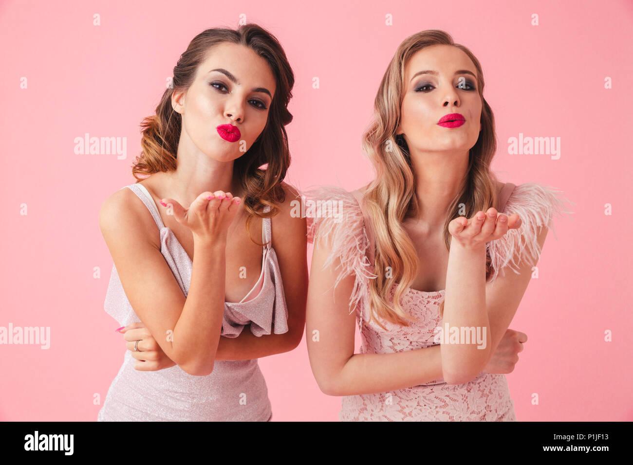 70ce3a803 Dos hermosas mujeres en vestidos envía besos de aire y mirando la cámara  sobre fondo de color rosa