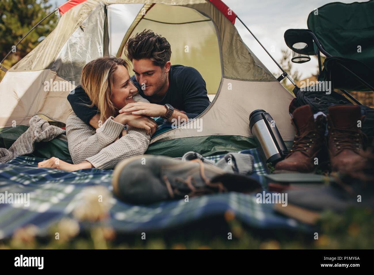 Hermosa pareja joven acostado en una tienda de campaña. Feliz pareja amorosa descansando en la carpa en el camping. Imagen De Stock