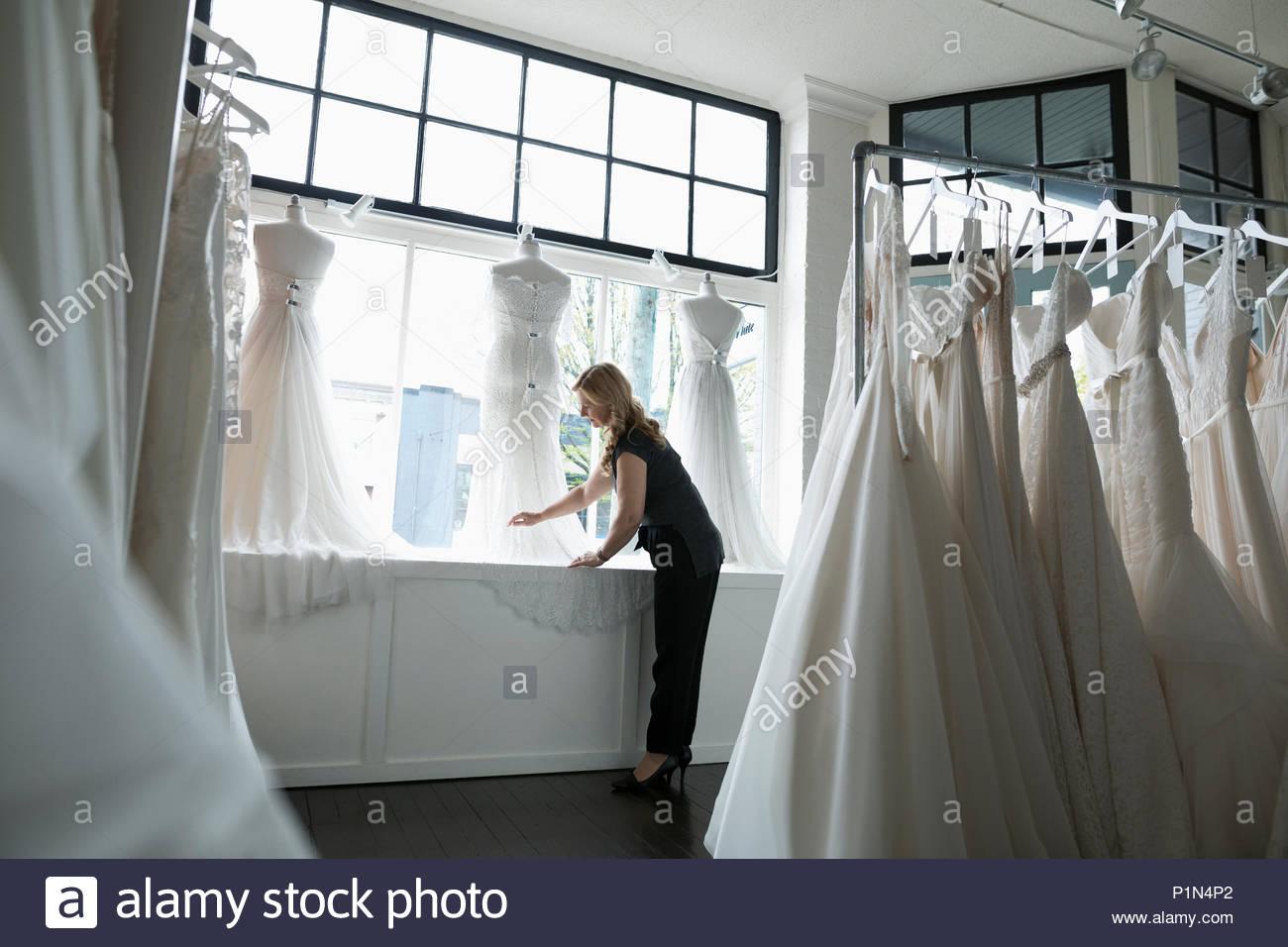 Propietario de boutique nupcial organizar vestido de bodas escaparate Imagen De Stock