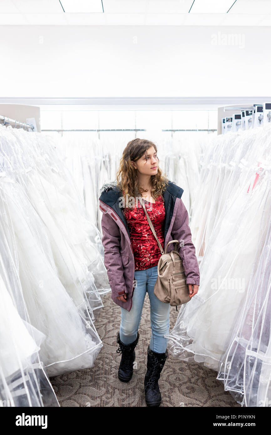 Mujer joven para compras de vestido de boda batas en pasillo del almacén de descuento boutique, bolso muchas prendas blancas colgadas en perchas rack fila Imagen De Stock