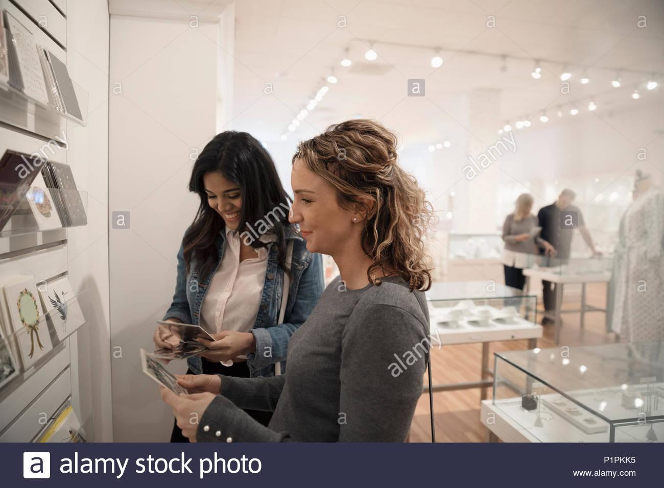 Las mujeres amigos para compras de tarjetas de felicitación en la boutique Imagen De Stock