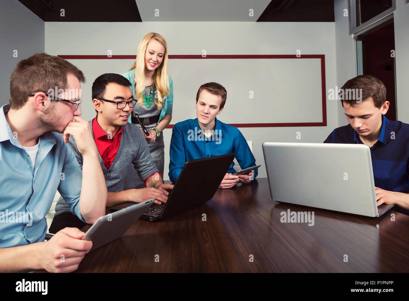 Jóvenes profesionales milenario trabajando juntos en una sala de conferencias en un negocio moderno de alta tecnología; en Sherwood Park, Alberta, Canadá Imagen De Stock