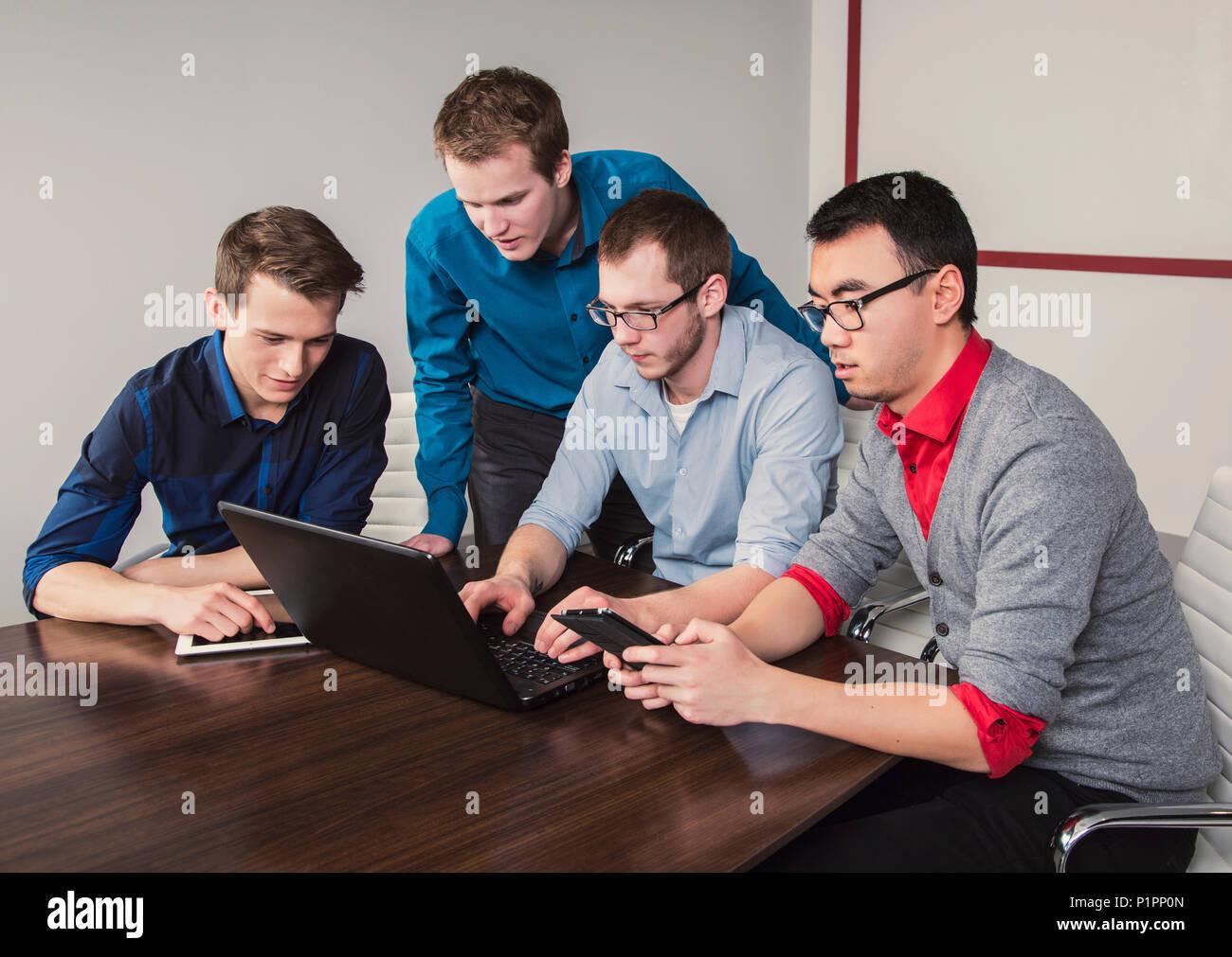 Los hombres jóvenes que son profesionales milenario trabajando juntos en una sala de conferencias en un negocio moderno de alta tecnología Imagen De Stock