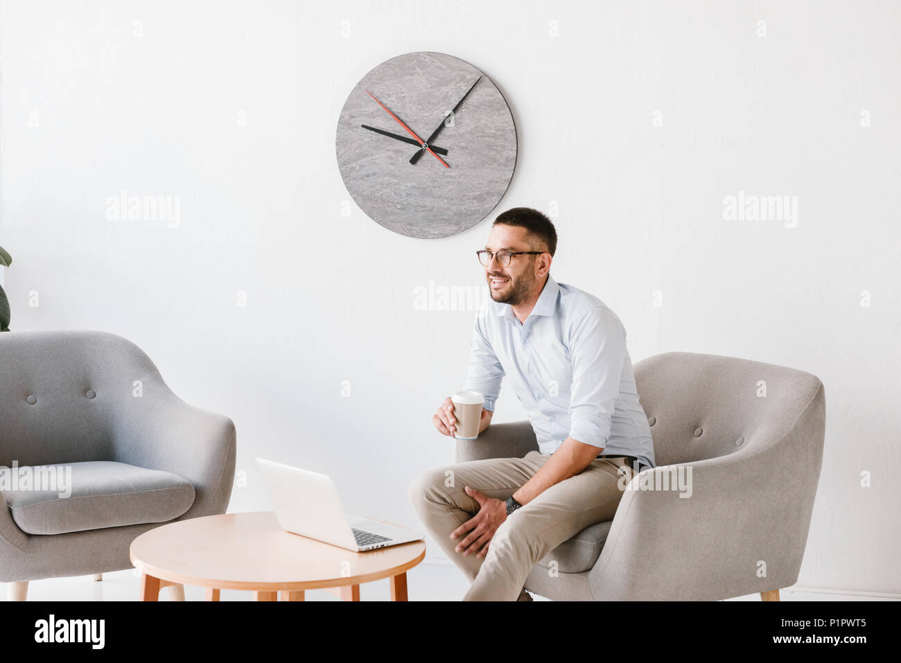 60b97148656 Imagen del hombre oficina diligente 30s en camisa blanca sentado en el  sillón y beber café para llevar mientras trabajando en el portátil en el  centro de ...