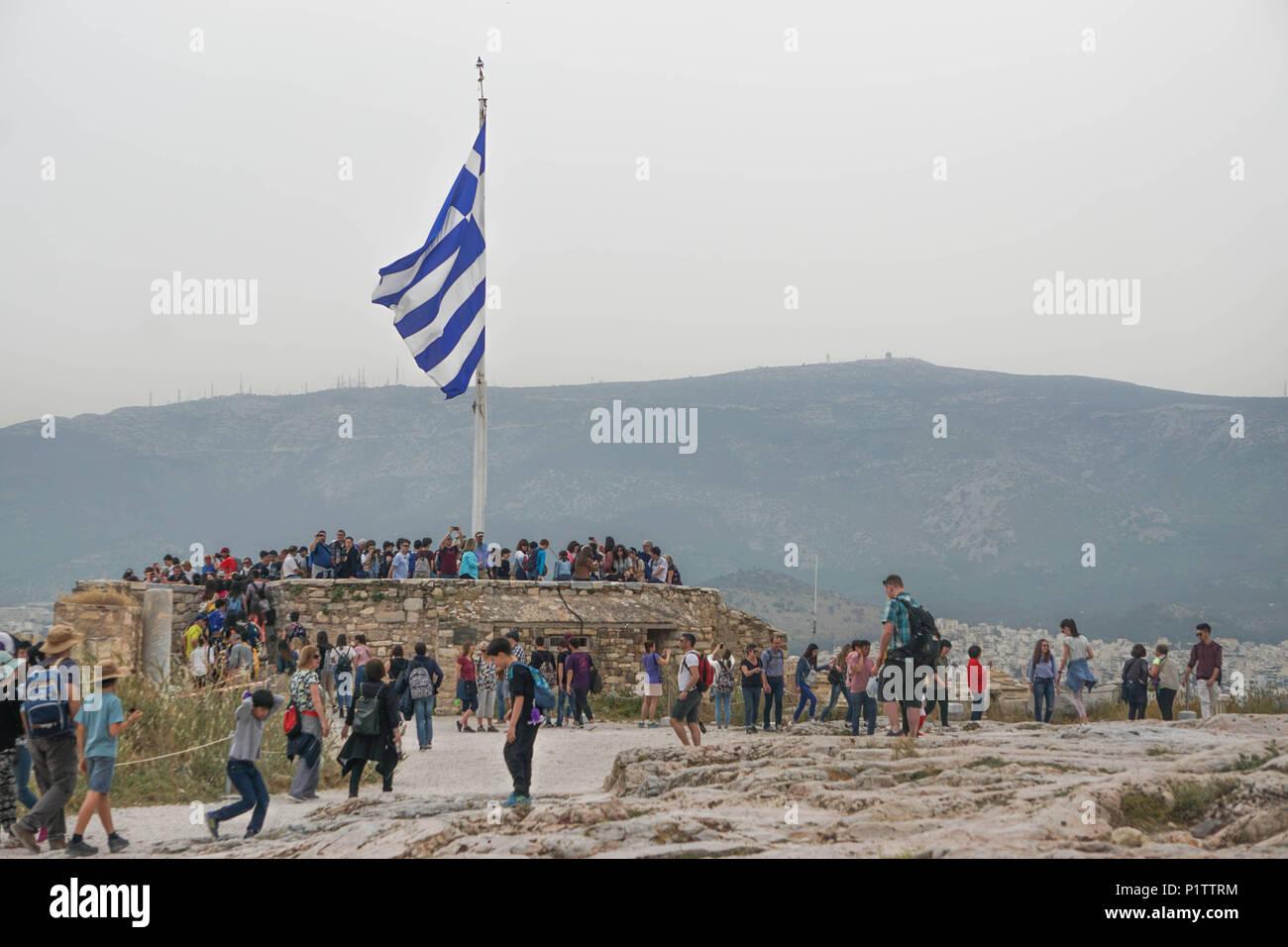 Atenas, Grecia - Abril 16, 2018: Los turistas se reúnen alrededor de la bandera griega en la Acrópolis de Atenas, bajo un cielo brumoso causados por la contaminación de polvo. Imagen De Stock