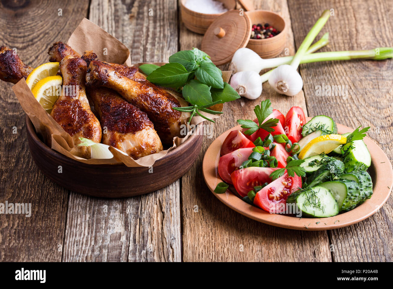 Muslos de pollo asado en cuenco de cerámica y hortalizas frescas sobre mesa de madera rústica, comida favorita Foto de stock