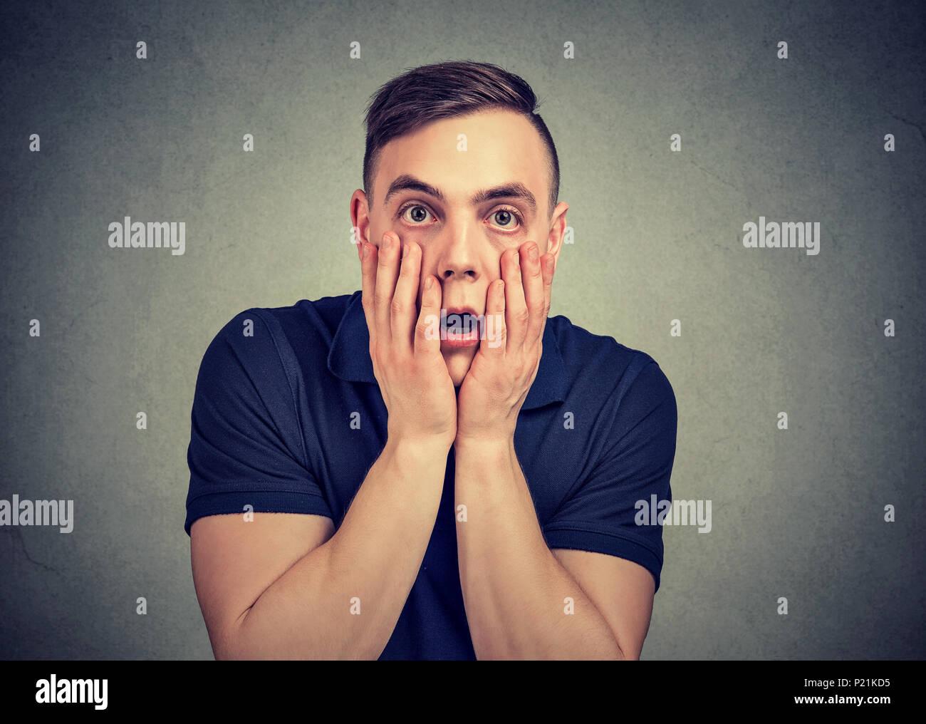 Joven hombre casual toca enfrentar en desesperación posando en gris y mirando a la cámara con miedo. Foto de stock