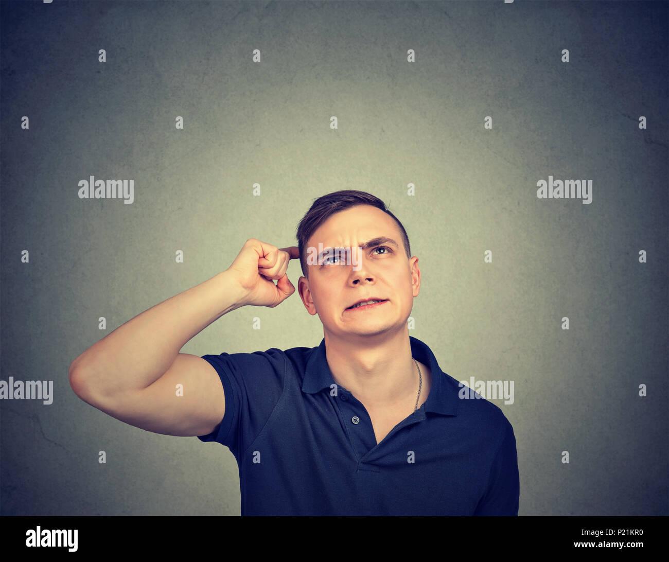 Closeup retrato hombre rascarse la cabeza, pensando en algo, mirando hacia arriba, aislados en la pared gris de fondo. Imagen De Stock