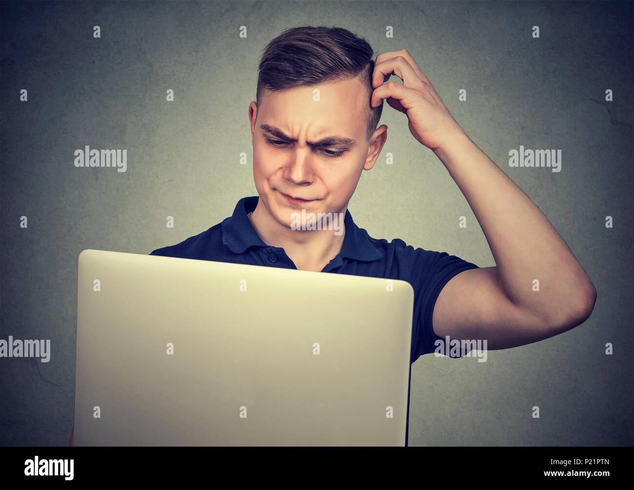Joven hombre casual mirando perplejos mientras usa el portátil tiene dificultades con el dispositivo. Imagen De Stock