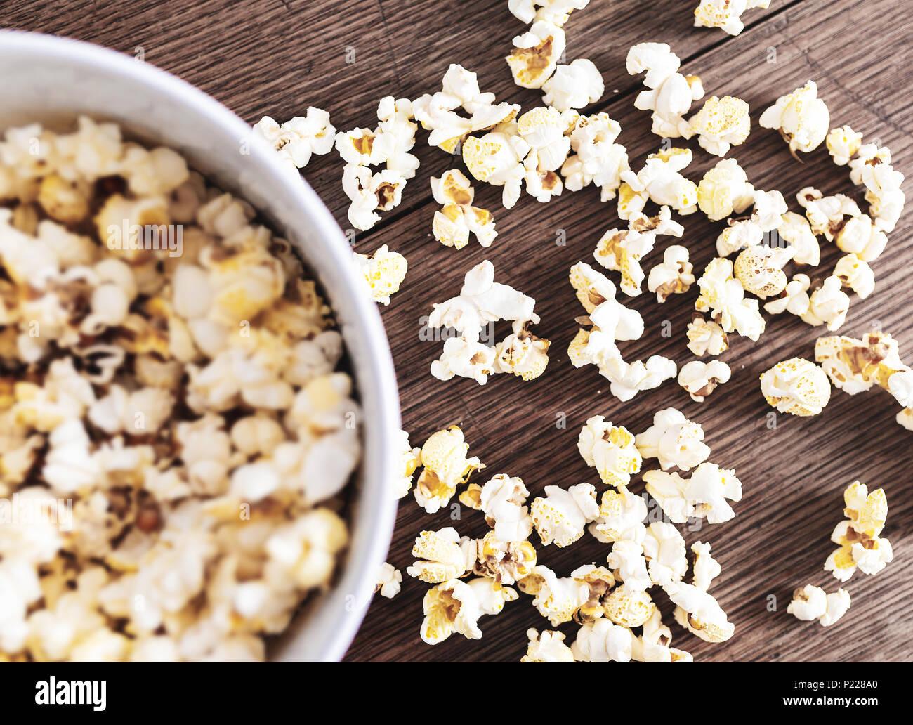 Directamente arriba cerca del cuenco lleno de palomitas de maíz sobre mesa de madera rústica Foto de stock