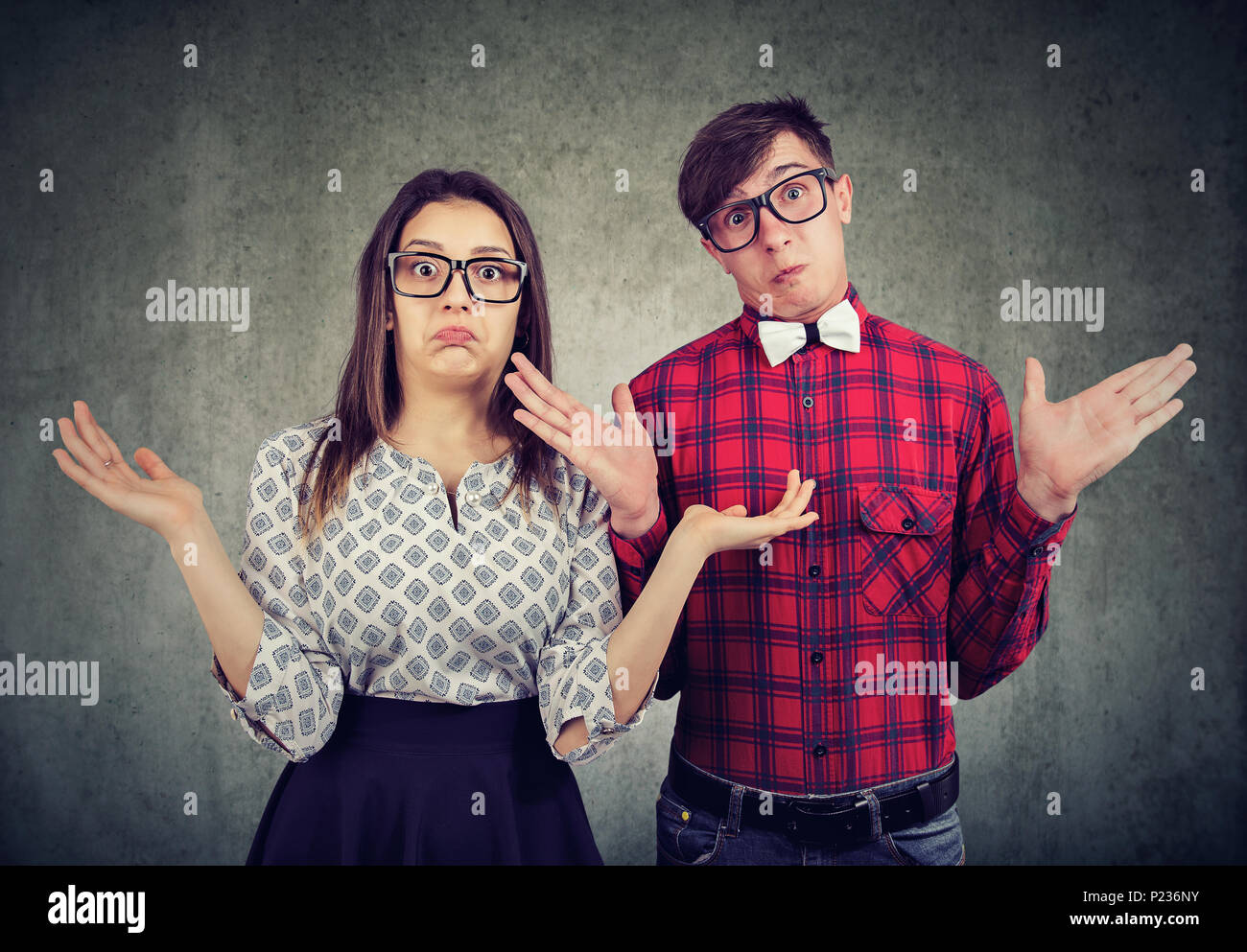Joven elegante par de gafas mirando desorientado y encogerse de hombros con mirando a la cámara. Imagen De Stock