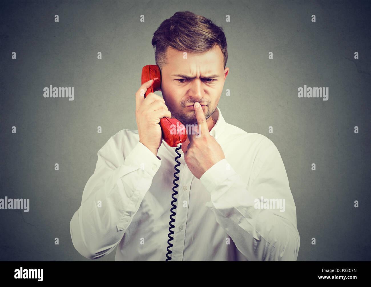 Pensativo en camisa blanca de hombre hablando por teléfono y tocar los labios en dudas tener noticias confusas. Imagen De Stock