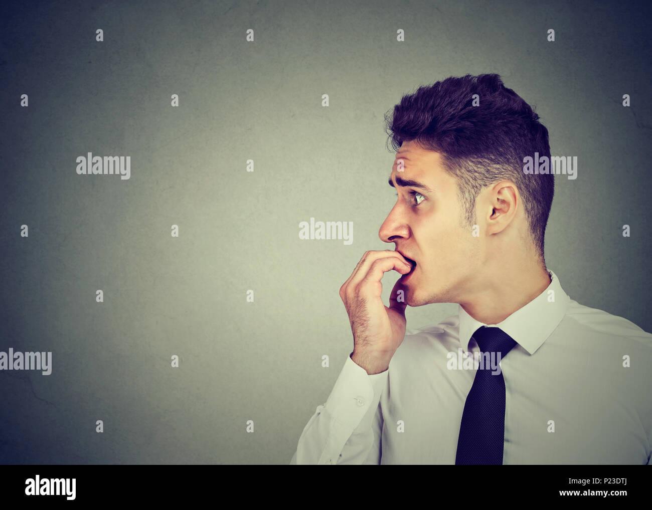 Preocupado ansioso joven mordiendo las uñas de los dedos de las manos mirando hacia el lado Imagen De Stock