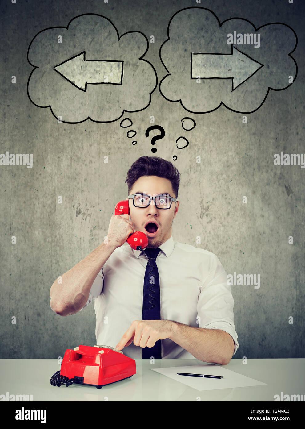 Formal joven hombre hablando por teléfono y sorprende con oportunidad confundida con la elección. Imagen De Stock