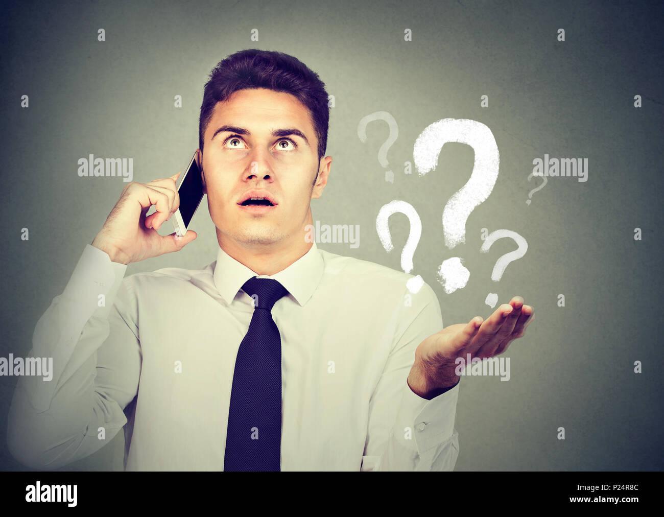Malentendido y lejana llamada concepto. Malestar molesto joven hablando por teléfono móvil tiene muchas preguntas aislado sobre fondo gris. Imagen De Stock