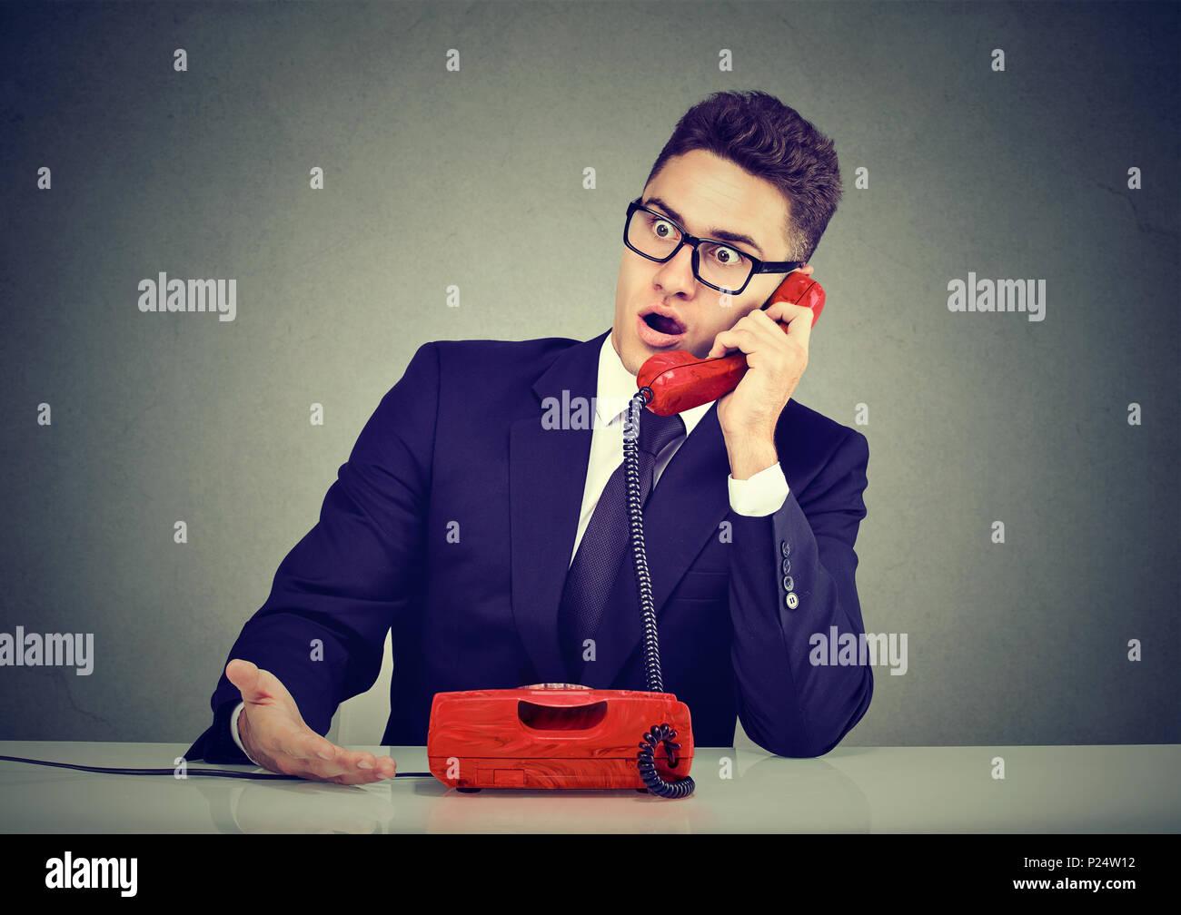 Conmocionado disgustado joven recibiendo malas noticias por teléfono Foto de stock