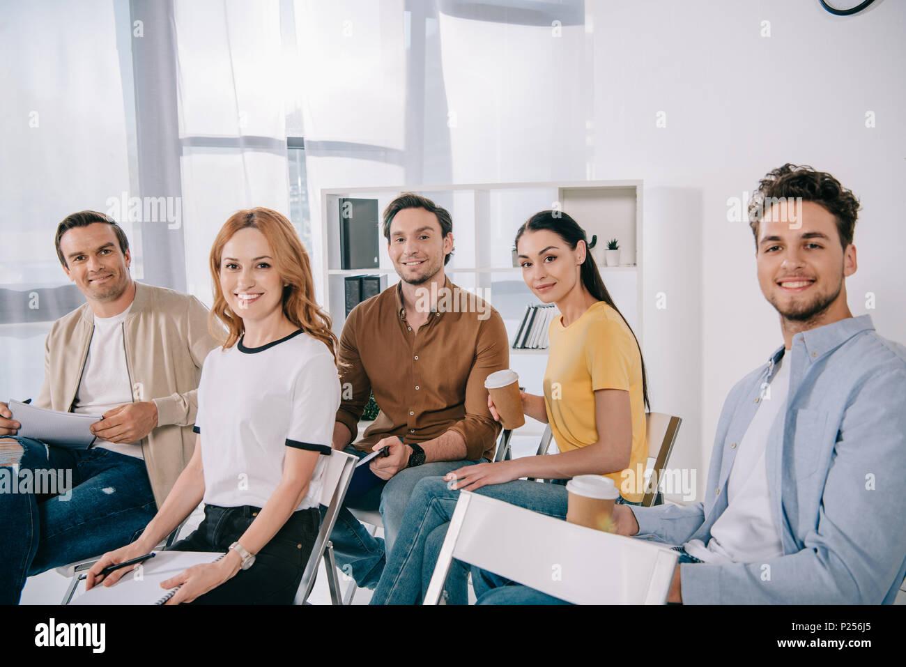 Gente de negocios sonriendo en ropa informal con la formación empresarial en Office Imagen De Stock