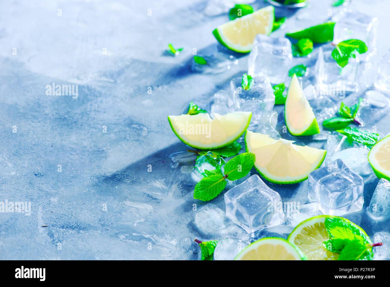 Menta, Limón y cubitos de hielo, cóctel mojito ingredientes cabezal con espacio de copia. Hacer bebidas de verano cerca. Luz solar y concepto de refrigerios. Foto de stock