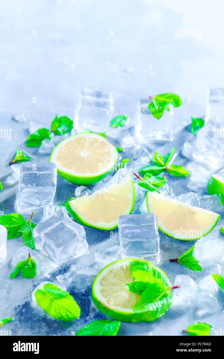 Menta, Limón y cubitos de hielo, cóctel mojito ingredientes cercano con espacio de copia. Hacer bebidas de verano cerca. Luz solar y concepto de refrigerios. Imagen De Stock