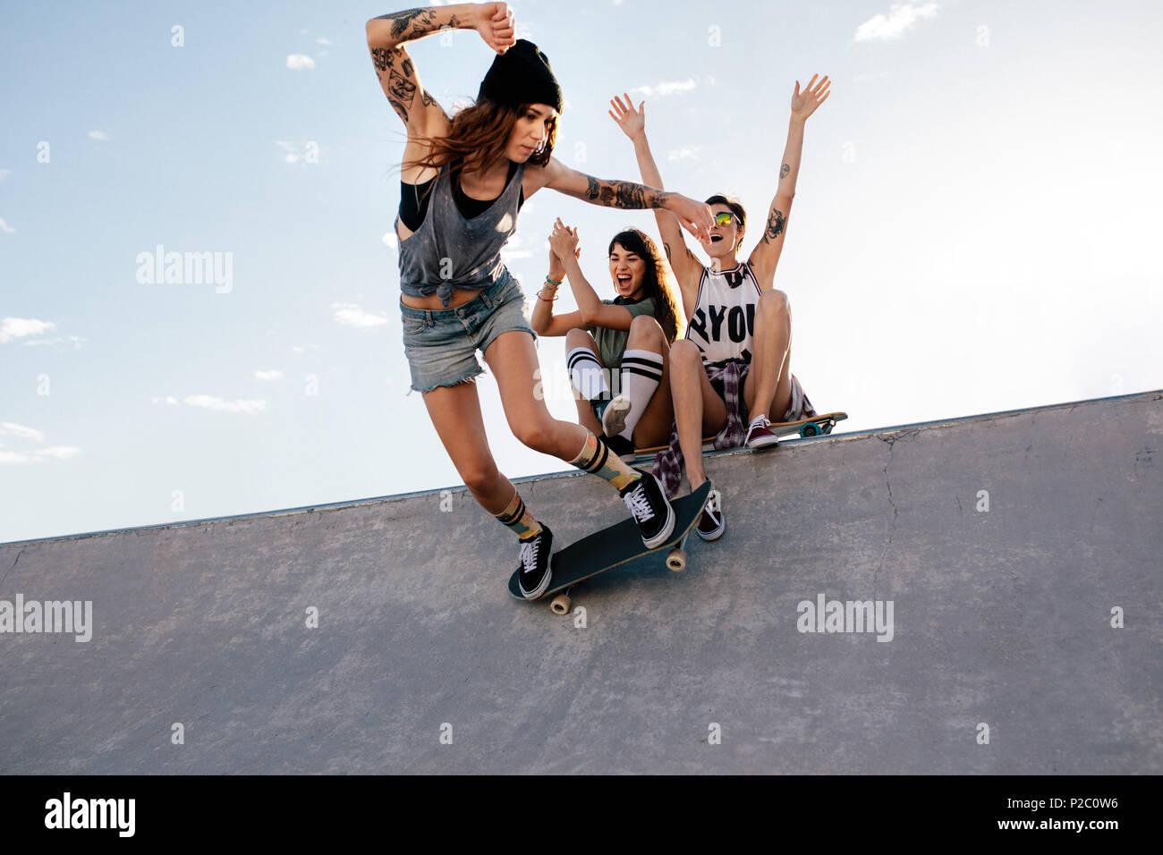 Skater girl cabalga sobre monopatín con amigas sentado en la rampa  animando. Hembra de skate 270275c572e
