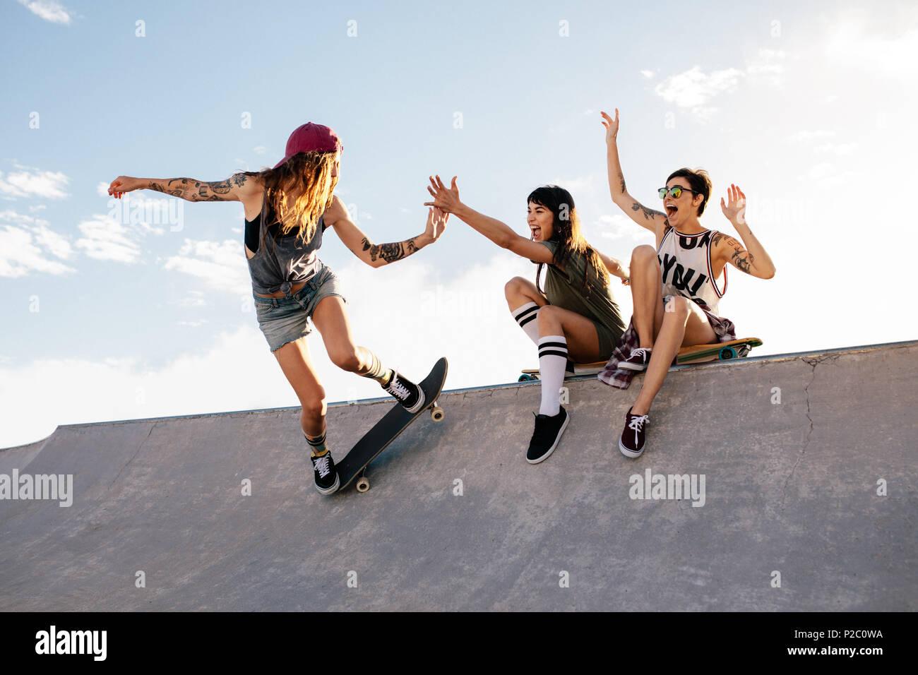 Patinador hembra montando en monopatín skate park con sus amigos sentado en  la rampa a divertirse 9d9ea3f78c3