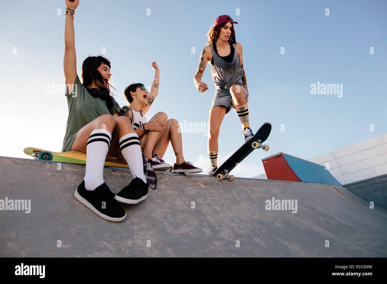 Tres jóvenes amigas en el parque de skate. Skater girl comenzando su rutina  con mujeres 3e837298cbb