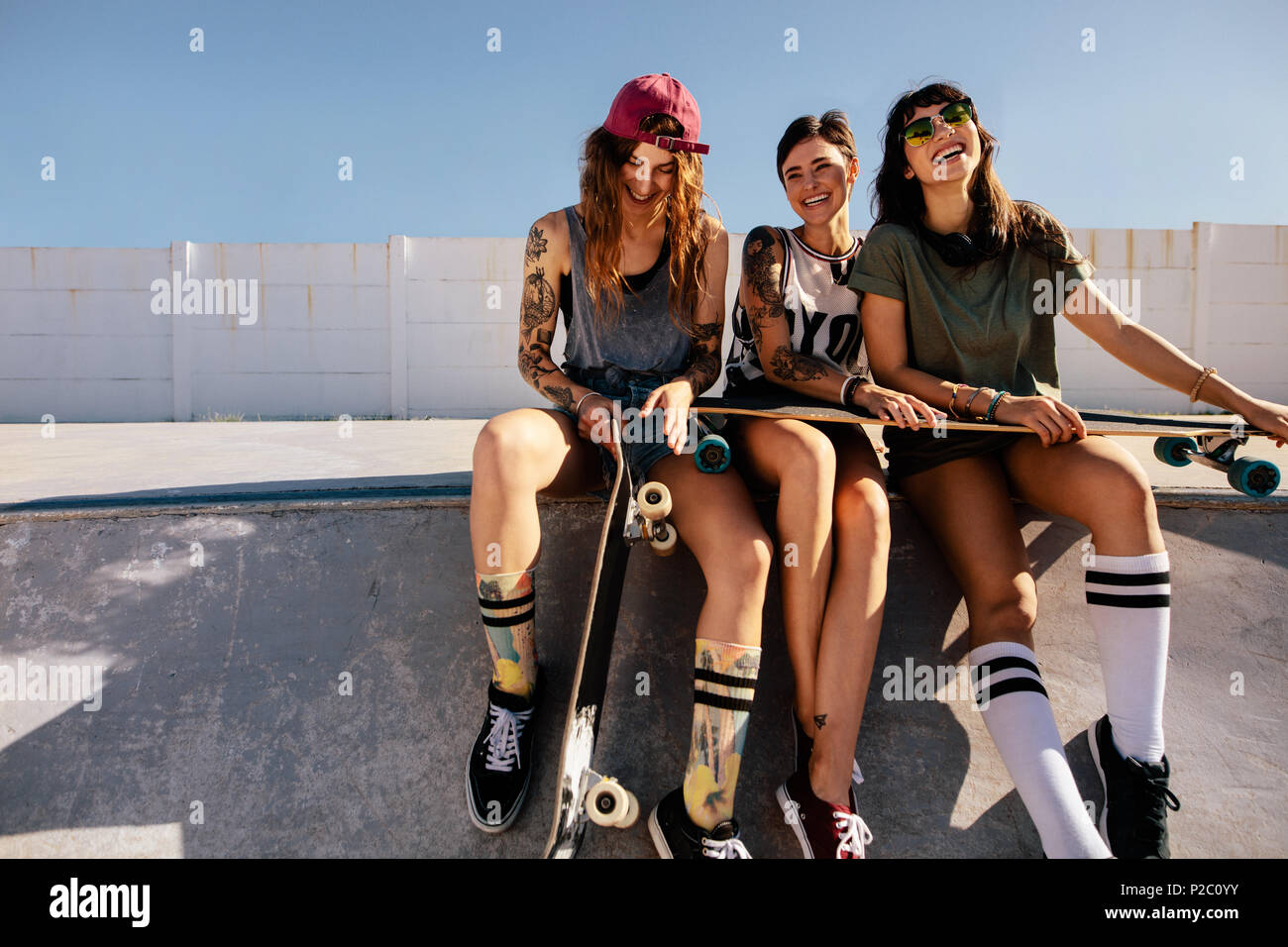 Feliz grupo de mujeres sentadas en la rampa en el parque de skate y  sonriente. a4a6b4e3311