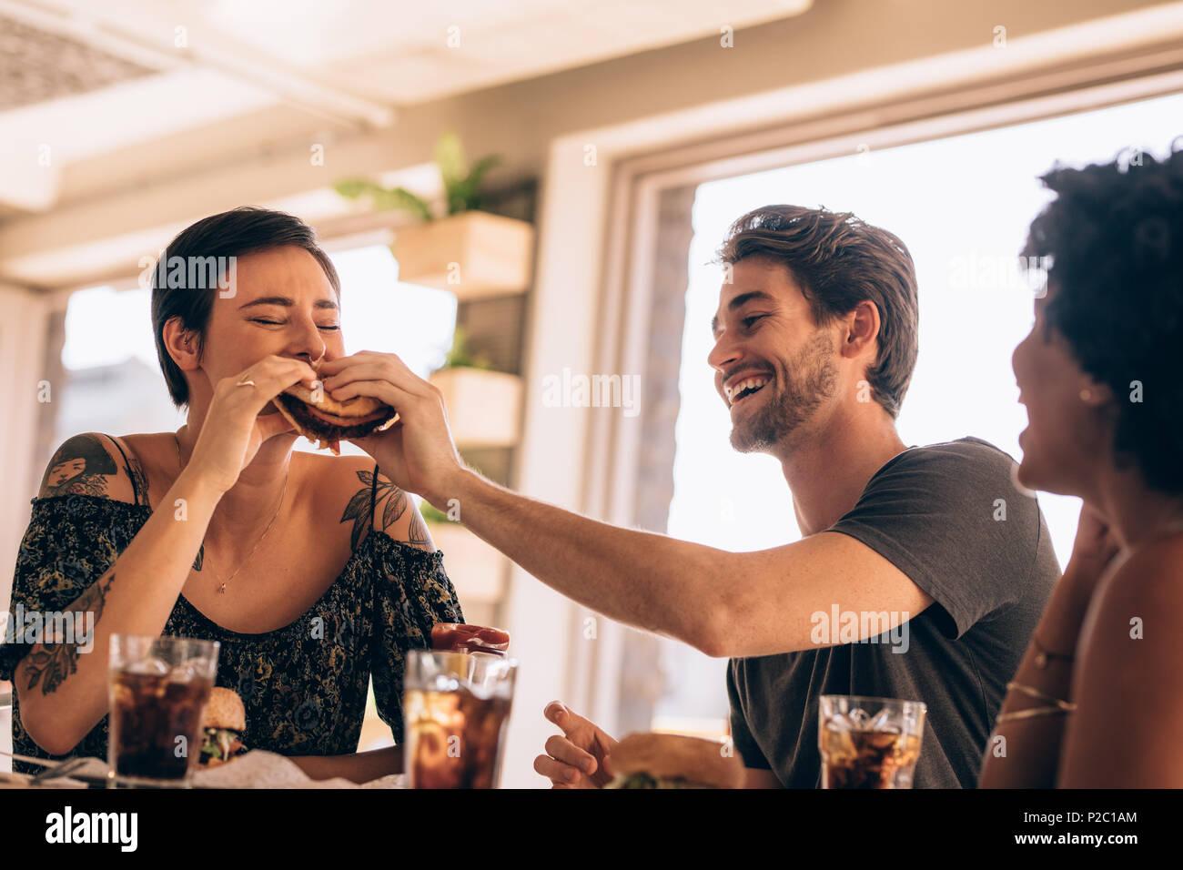 Mujer tomar una mordedura de amigos en un restaurante de hamburguesas. Grupo de jóvenes que tienen la comida en un restaurante. Imagen De Stock