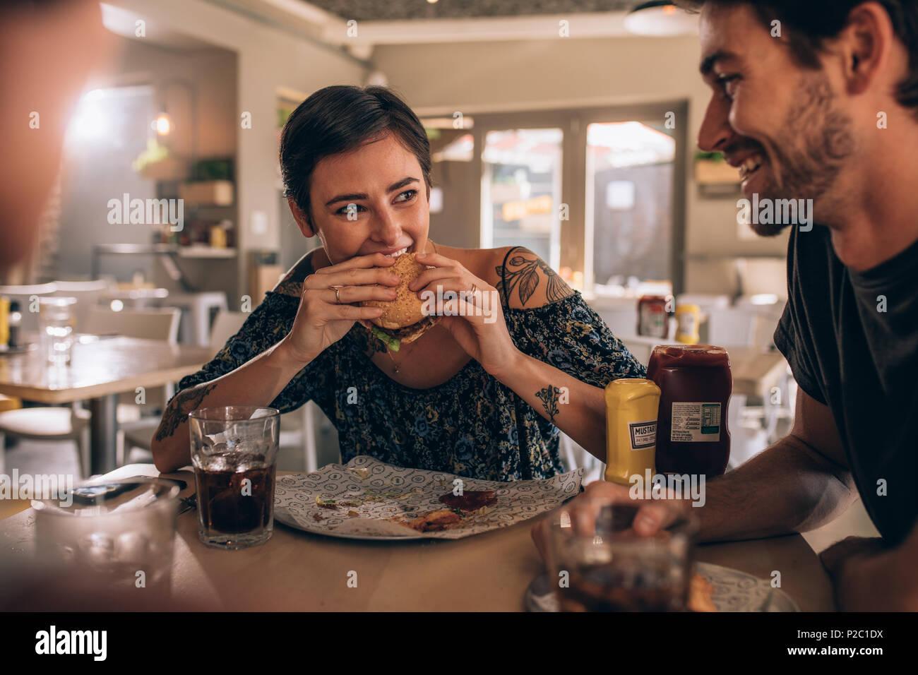 Joven comiendo hamburguesas mientras estaba sentado con amigos en el restaurante. Los jóvenes conversando y comiendo hamburguesas en la cafetería. Imagen De Stock