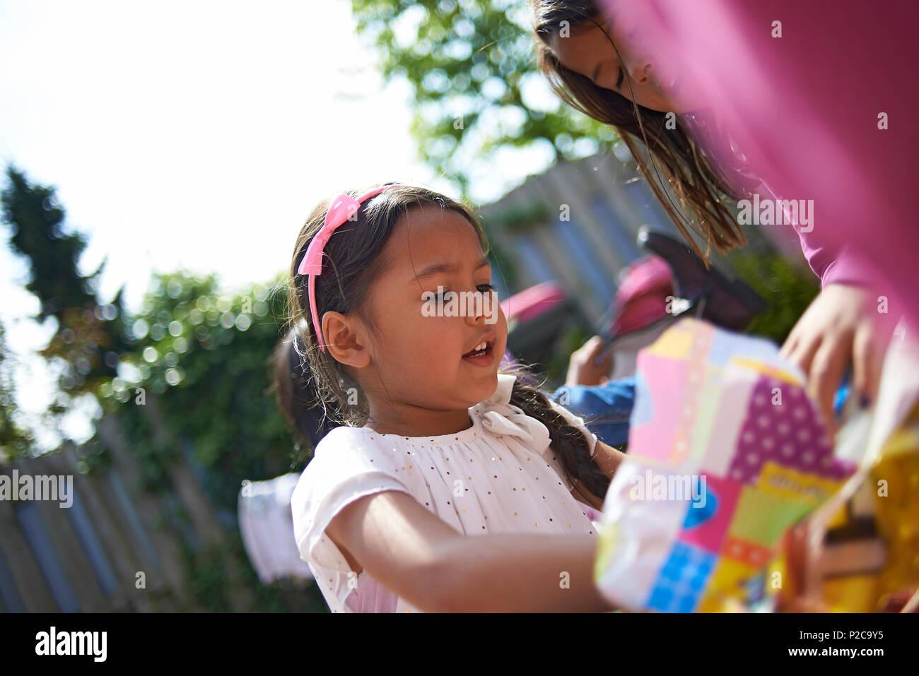 Cute Asian preadolescentes chica sentada en el jardín, rodeado de amigos y familia, vestida con un traje de princesa celebrando su cumpleaños desenvolver presente Imagen De Stock