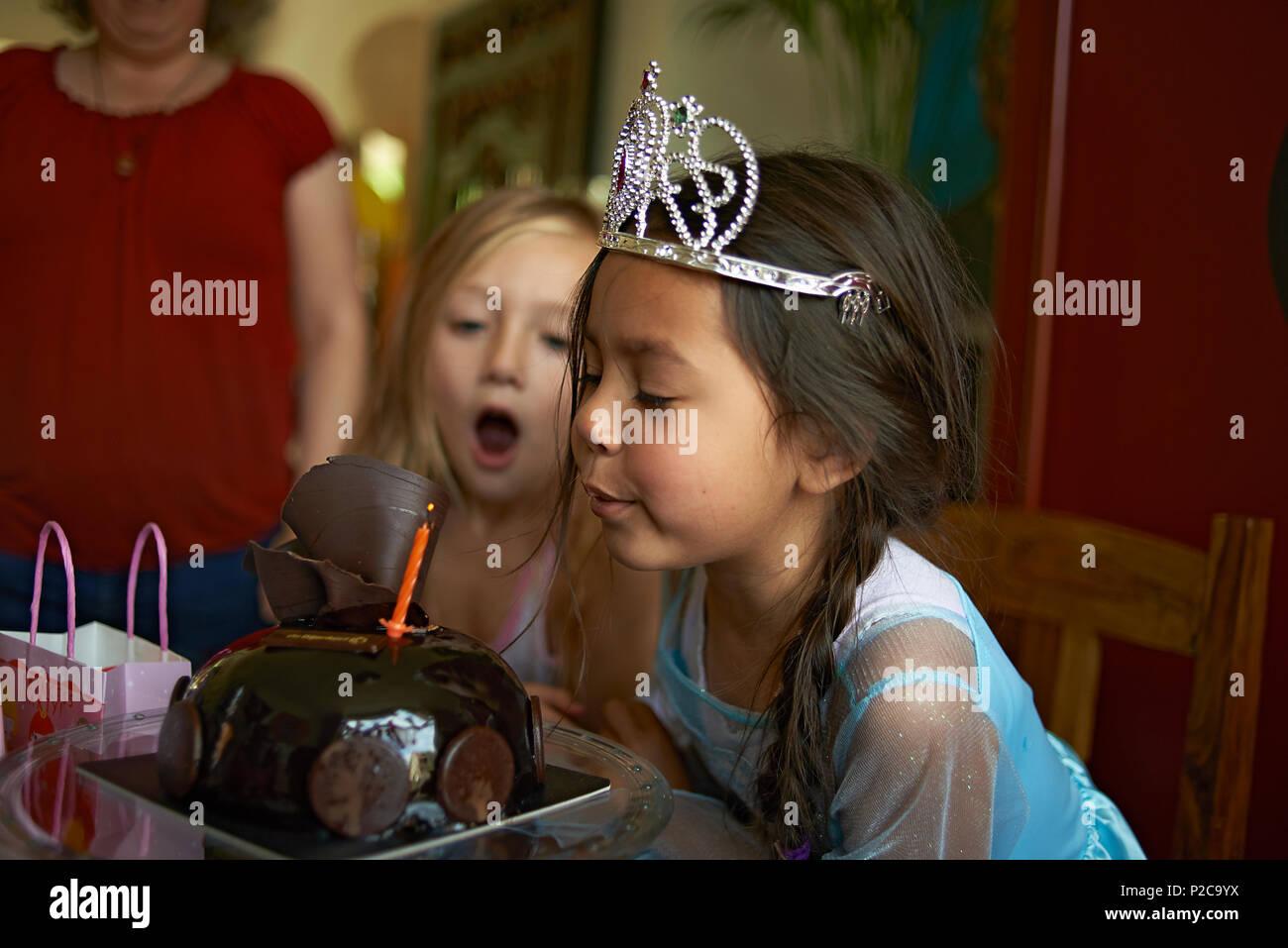 Cute little Asia preadolescentes vestida de un vestido de princesa y una tiara soplar las velas de su tarta de cumpleaños con su mejor amiga sentada junto a ella Foto de stock