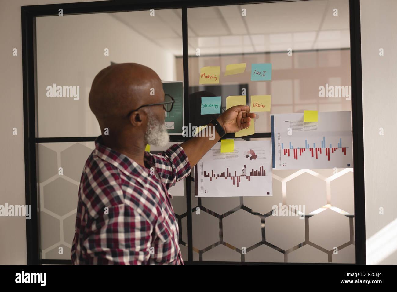 Diseñador gráfico Senior mirando notas rápidas Foto de stock