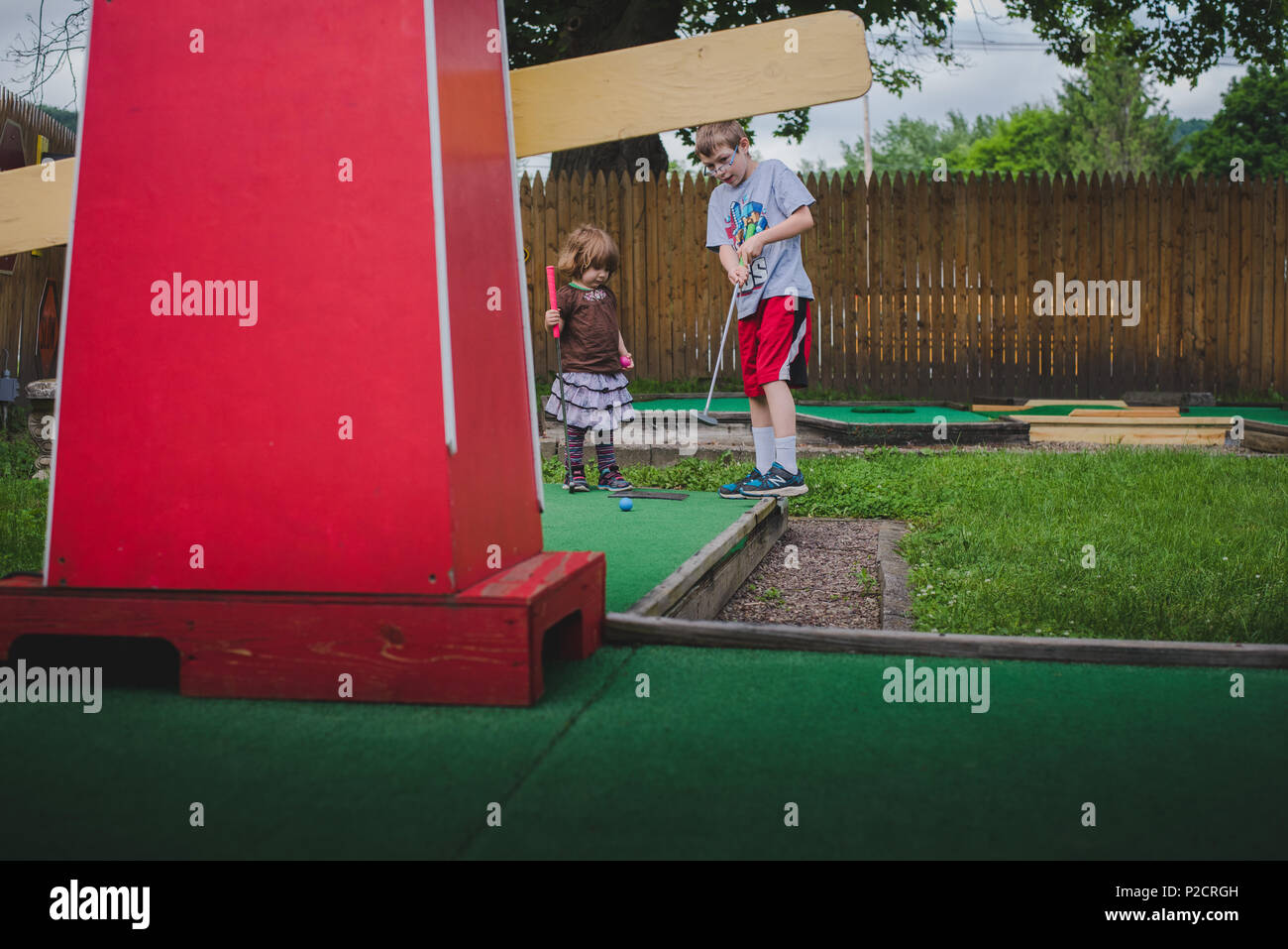 Una niña juega minigolf en clima cálido. Imagen De Stock
