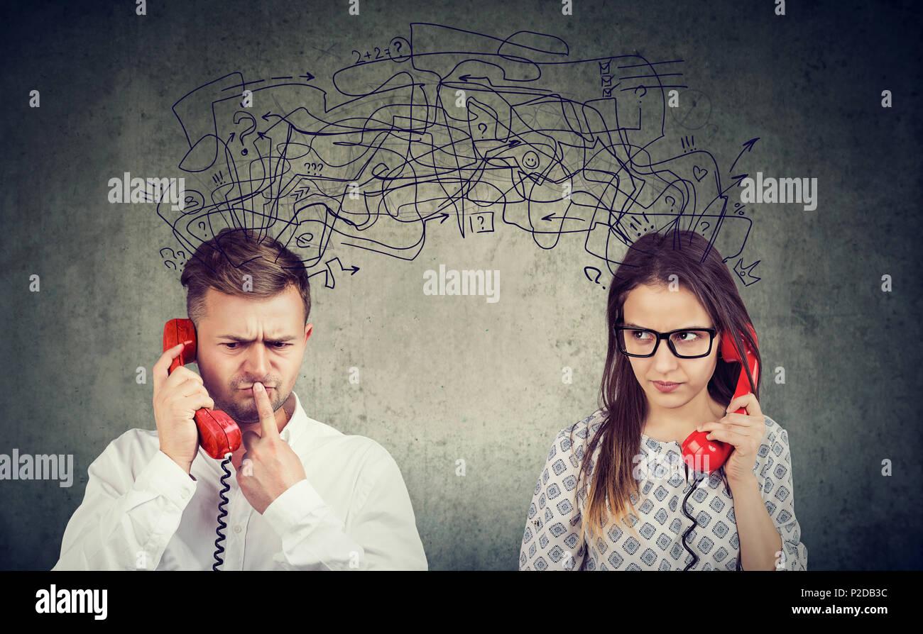 Preocupado confundida pareja mujer y hombre hablando por teléfono intercambiando con muchos pensamientos negativos. Imagen De Stock