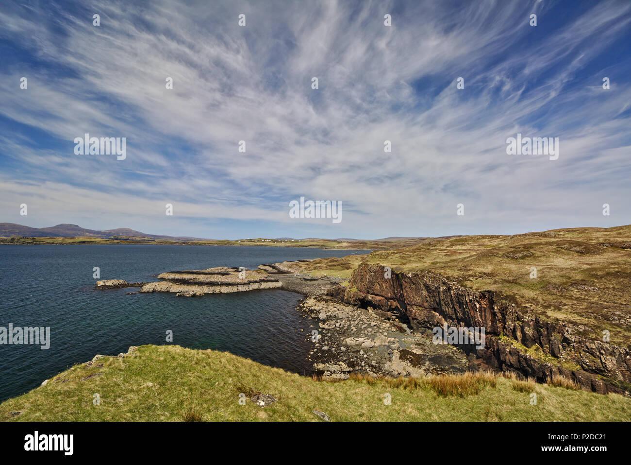Acantilado con baja cabecero en el fondo y un cielo azul con nubes cirrus blanco Foto de stock