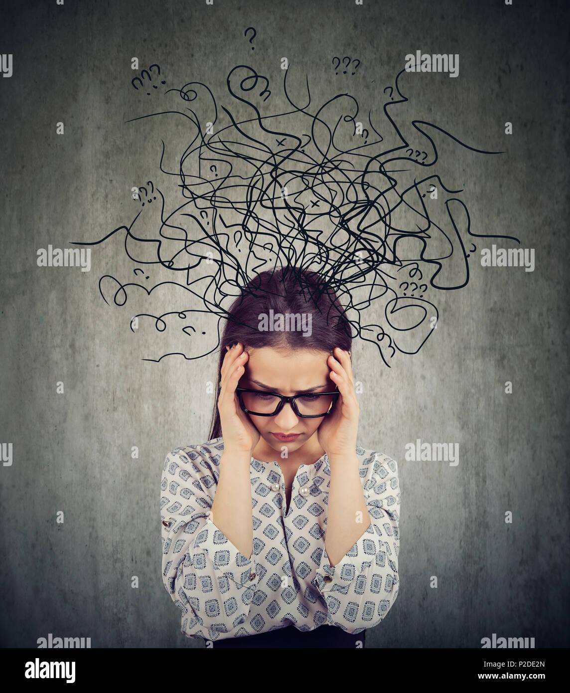 Chica con gafas que tengan problemas con la salud mental y busca en el caos profundo sobre fondo gris Foto de stock