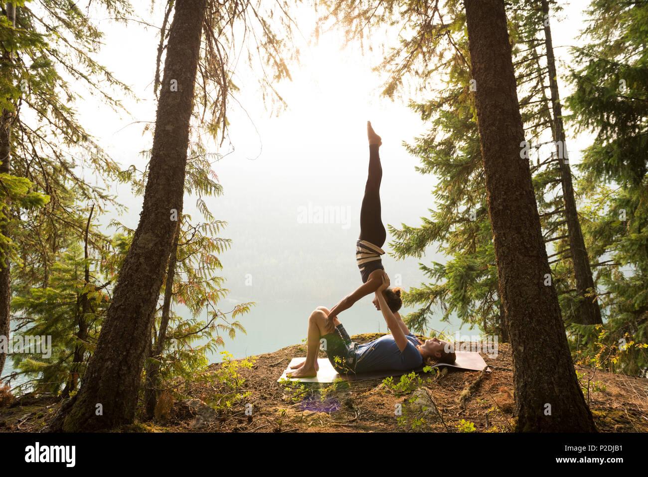 Pareja deportiva practicando yoga acro en un exuberante bosque verde Imagen De Stock