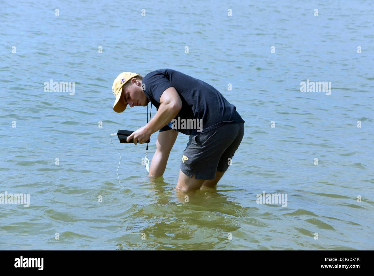 Hombre, verificar la temperatura del agua, la calidad del Lago Michigan playa para el Departamento de Recursos Naturales de Wisconsin, las agencias sanitarias locales Dos Ríos, WI Imagen De Stock