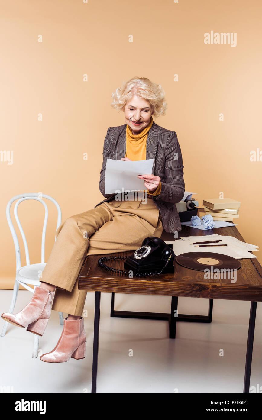 b98eb5fac2f07 Elegante mujer senior escrito en papel y sentarse en la mesa con el teléfono  giratorio y