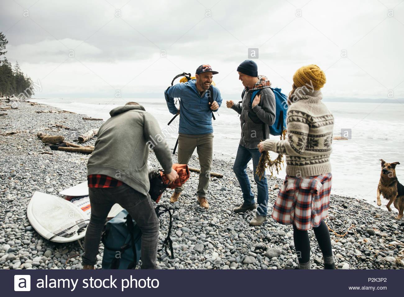 Amigos con perro disfruta de una escapada de fin de semana de surf en playa resistente Imagen De Stock