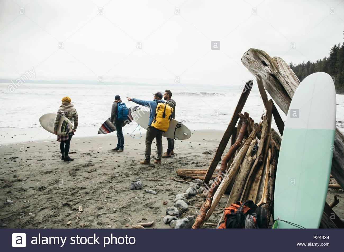 Amigos, disfrutando de una escapada de fin de semana de surf en playa resistente Imagen De Stock