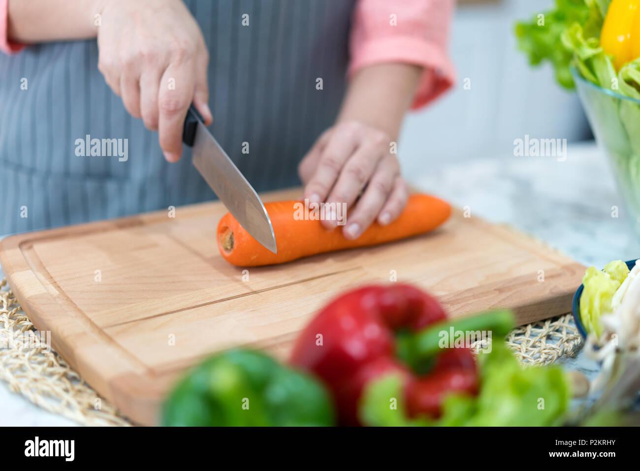 La mano con la zanahoria de corte de la cuchilla. La mujer prepara la comida en la mesa. El chef cocina deliciosa cena. Trabajo que requiere habilidad. Imagen De Stock