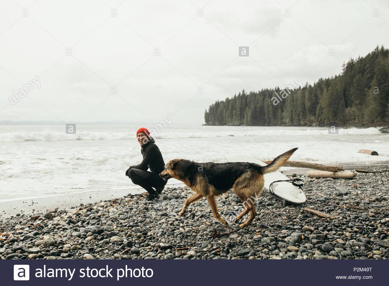 Surfista masculino con perro en la playa resistente Imagen De Stock