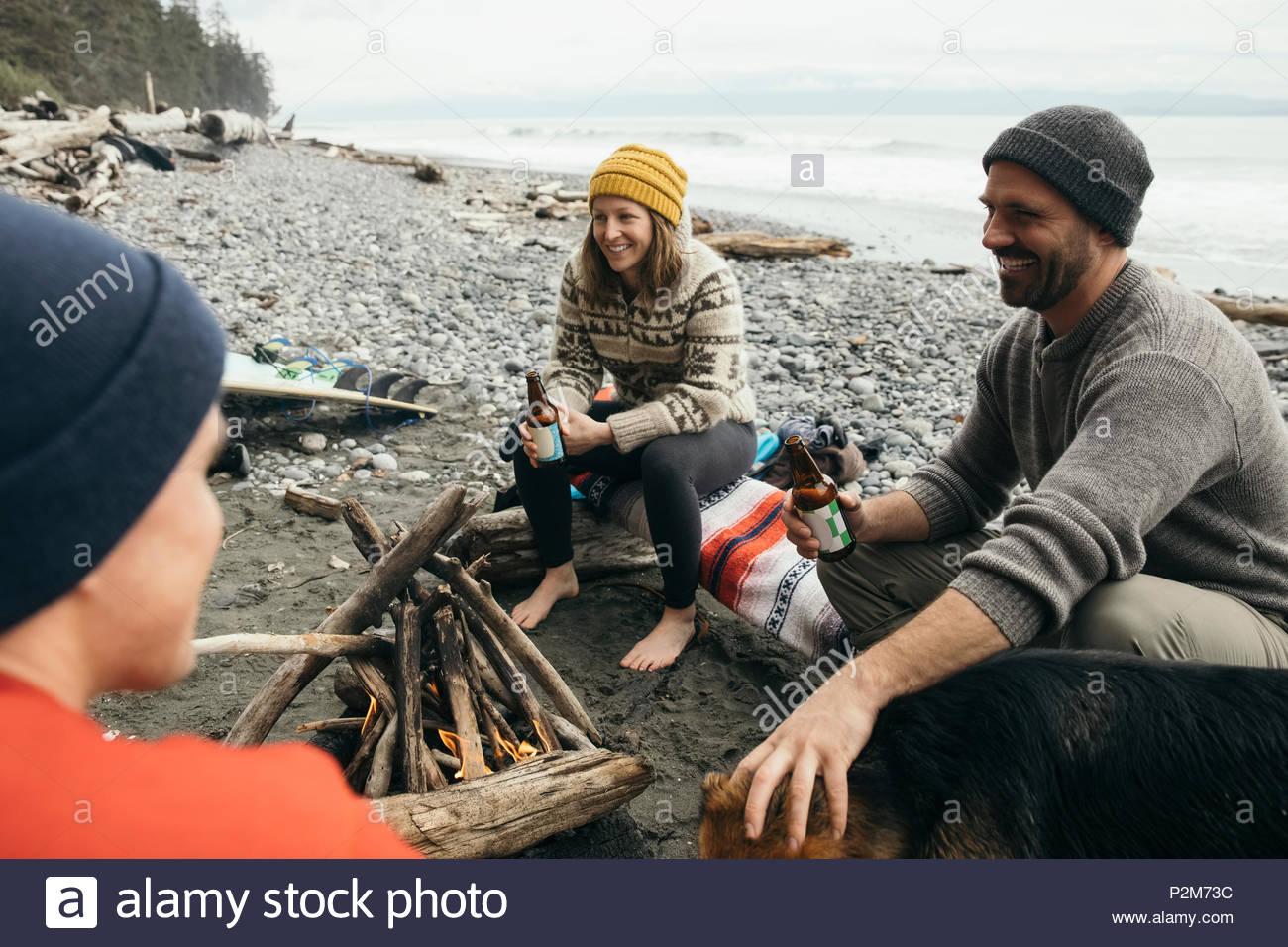 Amigos, disfrutando de una escapada de fin de semana de surf, bebiendo cerveza en una fogata en la playa resistente Imagen De Stock