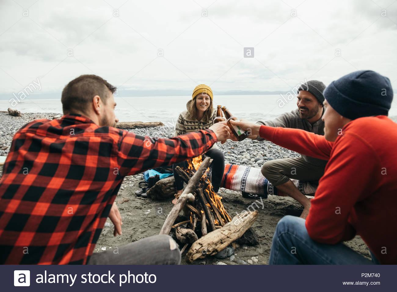 Amigos, disfrutando de una escapada de fin de semana de surf, cerveza de tostado en fogata en playa resistente Imagen De Stock