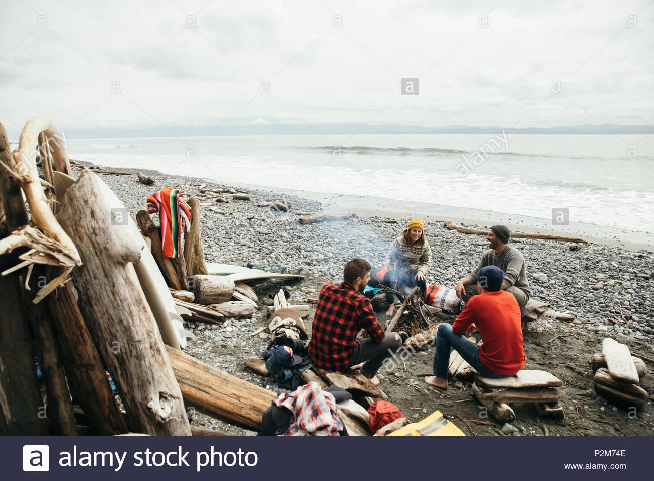 Amigos, disfrutando de una escapada de fin de semana de surf, relajándose en una fogata en la playa resistente Imagen De Stock