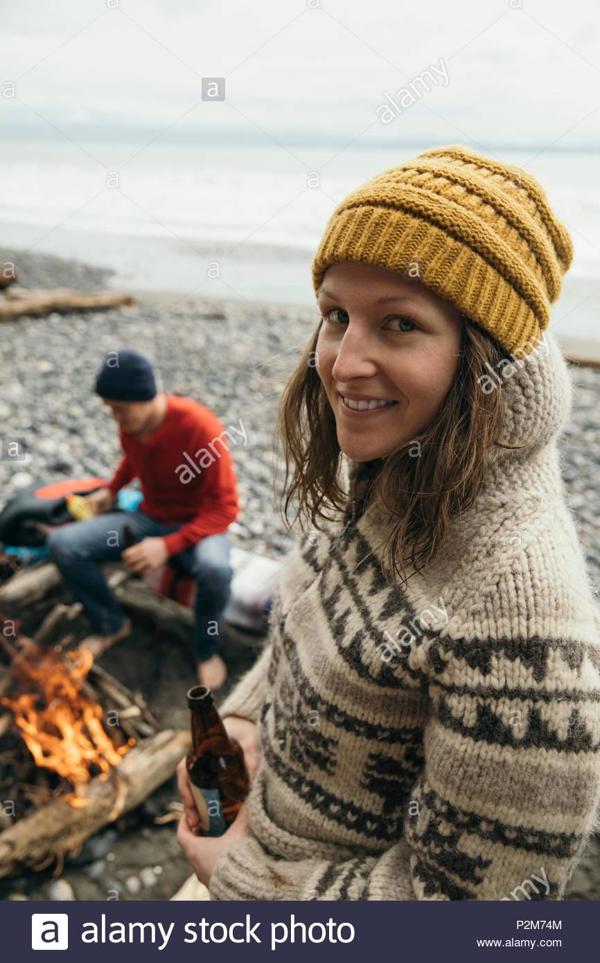 Retrato sonriente, seguro mujer bebiendo cerveza, disfrutando de una escapada de fin de semana en el campamento de surf en playa resistente Foto de stock