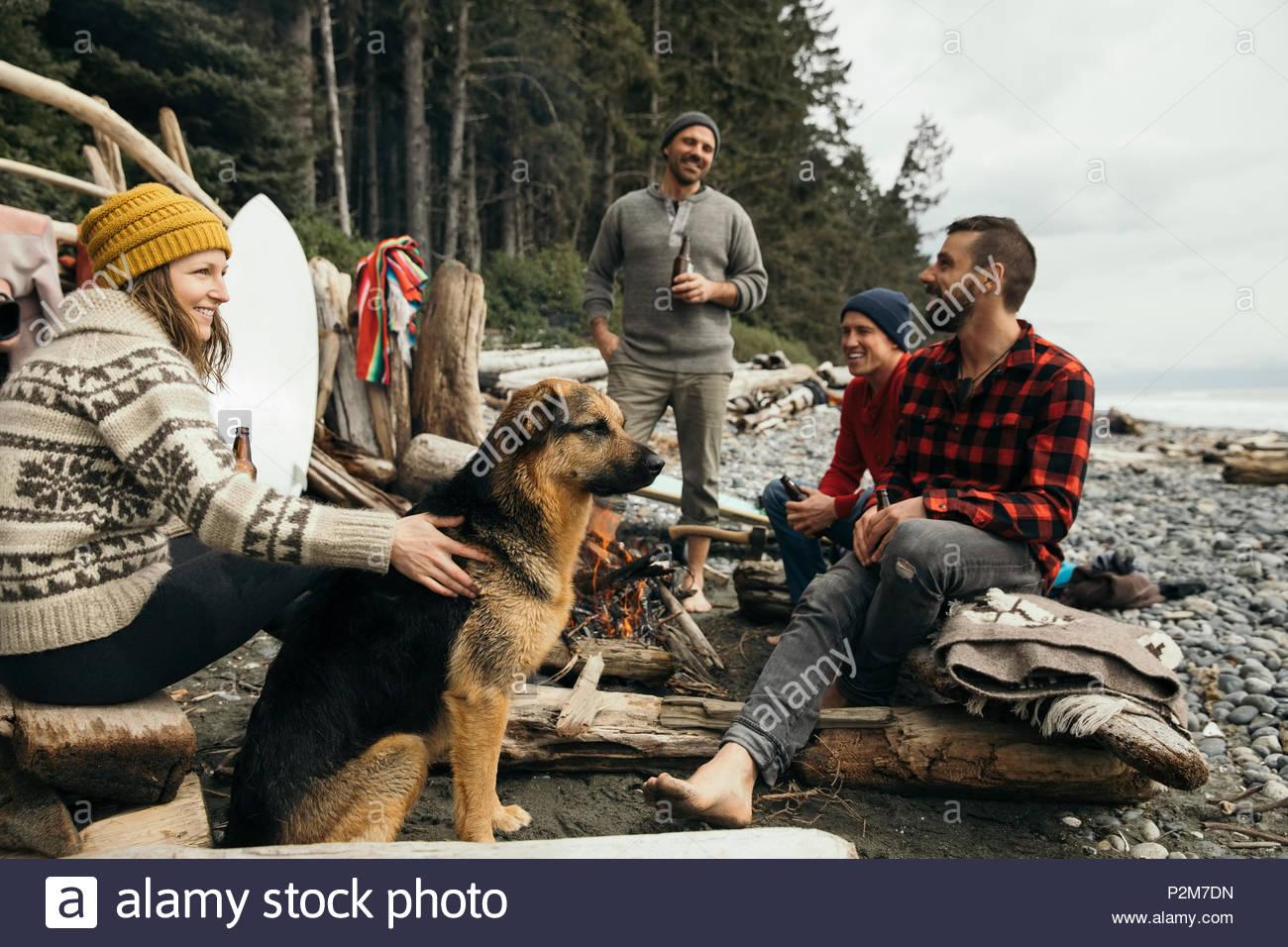 Amigos con perro disfruta de una escapada de fin de semana de surf, relajándose en la playa de camping en los robustos Imagen De Stock