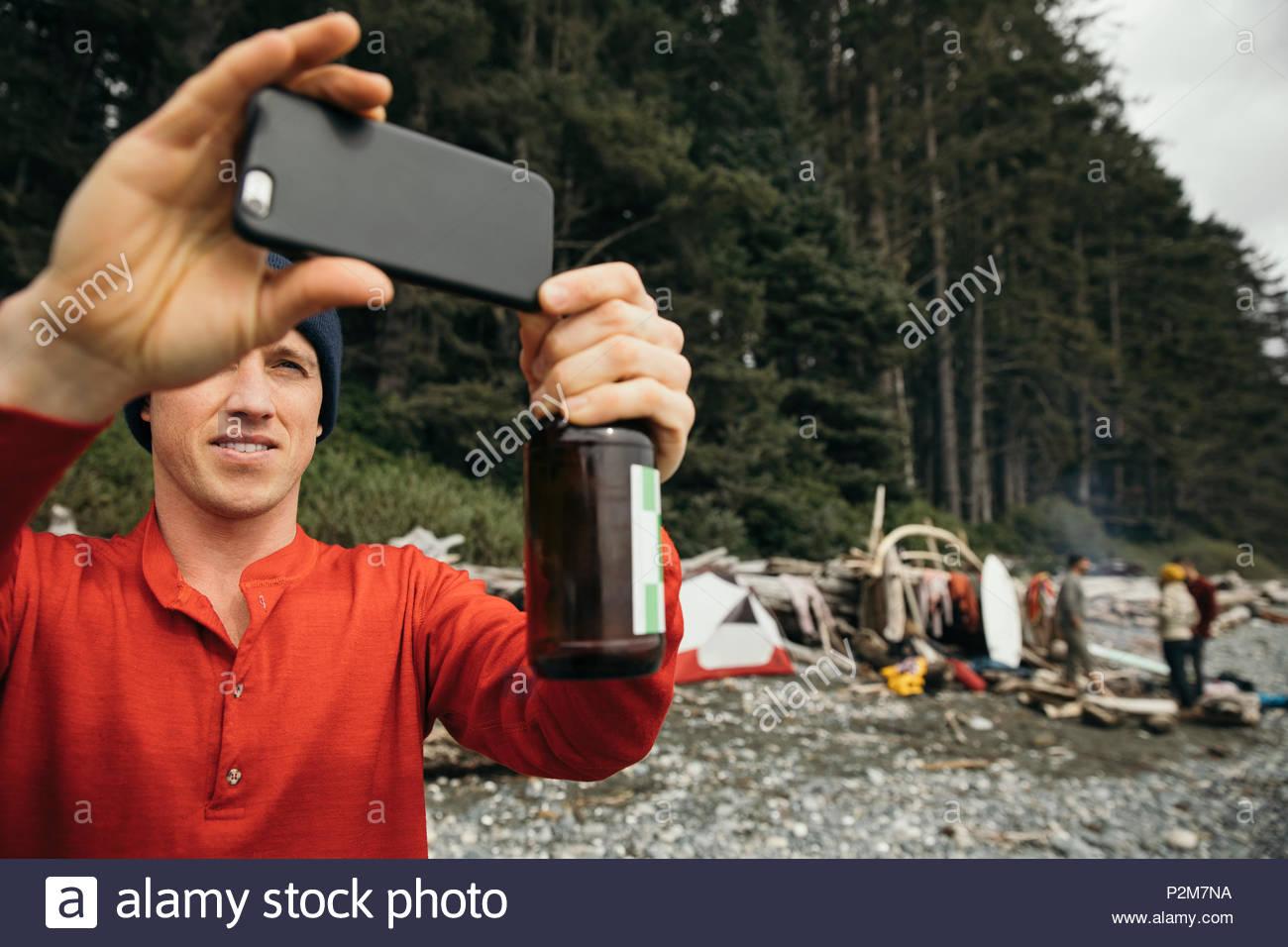 El hombre disfruta de una escapada de surf de fin de semana con los amigos, beber cerveza y utilizando la cámara del teléfono en playa resistente Imagen De Stock